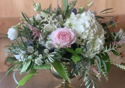 flower arrangement in brass pedestal container
