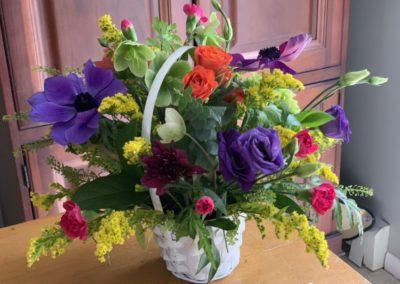 bright flower arrangement in white basket with handle