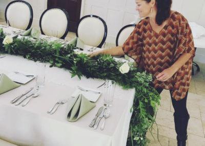 woman placing greenery across set table