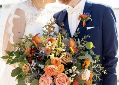 orange wedding bouquet with bride and groom