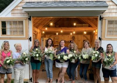 women showing arrangements after floral class